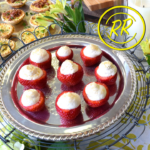 Nine strawberries stuffed with white cashew cream sit on a shiny silver plate.