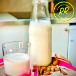 One clear glass bottle of creamy white almond milk stands next to a glass half full of almond milk. Whole, raw almond spill in front of the bottle on a pink and brown tablecloth.