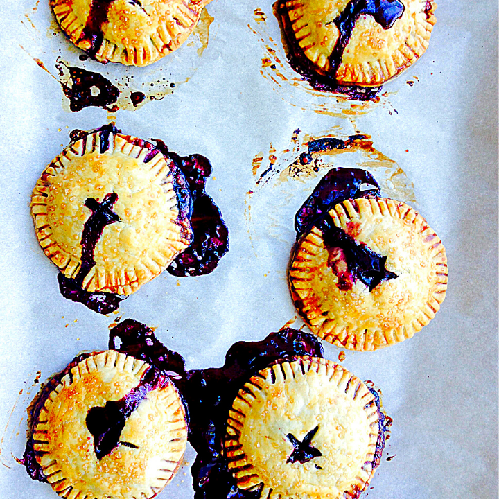Six Circular small, golden hand-pied ooze blueberry juice on a sheet pan