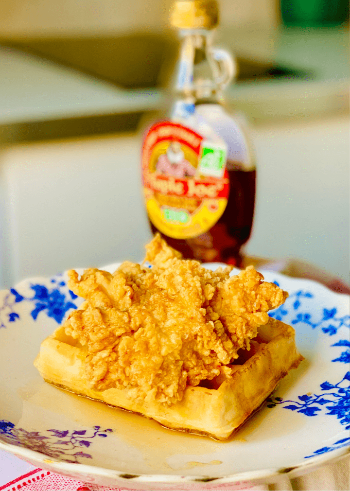 A crispy piece of chicken on a golden waffle with maple syrup.